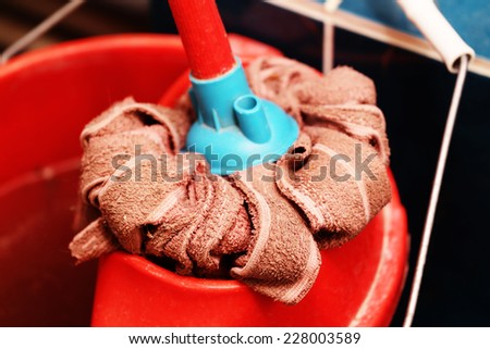 Red mop and bucket closeup - stock photo
