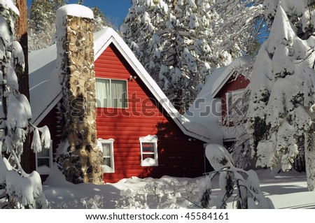 Red mountain cabin stands out in snow - stock photo