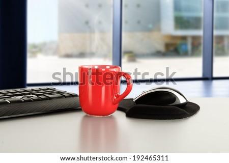 red mug and computer  - stock photo