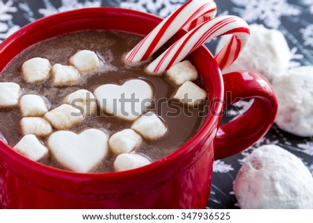 Red mug filled with hot chocolate with heart shaped marshmallows, peppermint candy canes and snowball cookies on black and white snowflake background - stock photo
