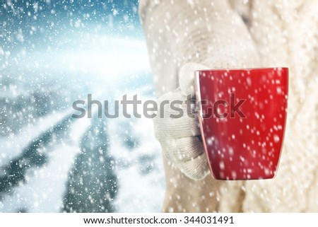 red mug of coffee and winter day and woman hand  - stock photo