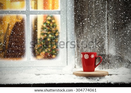 red mug on window sill and xmas tree in home  - stock photo