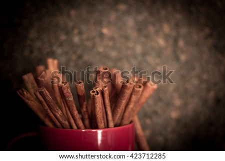 red mug with cinnamon on the cork background