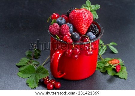 red mug  with fresh berries on black stone background, low key - stock photo