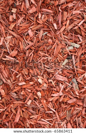 Red mulch background. Wood mulch for garden. Landscape wooden chips red color. Wooden mulch texture background. Landscaping red colored materials. Woodchips shavings patterns background. Wood mulch  - stock photo