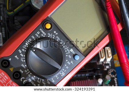 Red multimeter on motherboard background. Instrument for measuring voltage - stock photo