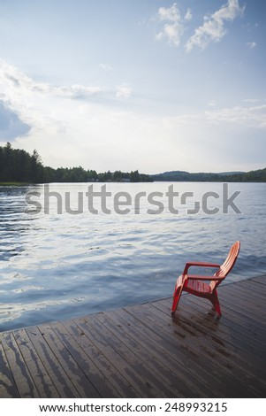 Red Muskoka Chair Sitting on Dock by Lake with Evening Sunlight - stock photo