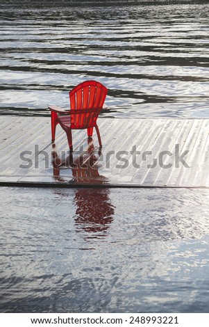Red Muskoka Chair Sitting on Water Level Dock by Lake - stock photo