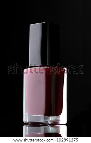 Red nail polish on black background - stock photo