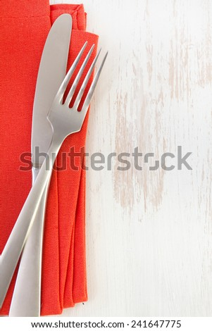 red napkin with knife and fork on white background - stock photo