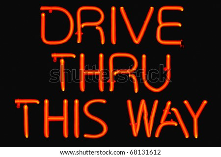 Red neon sign for a fast food restaurant drive thru. - stock photo