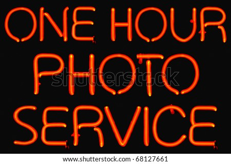 Red neon sign for one hour photo service.