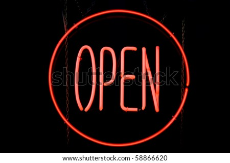 Red neon sign of a circle containing the word 'Open' on a black background. - stock photo