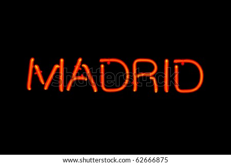 Red neon sign of the word 'Madrid' on a black background.