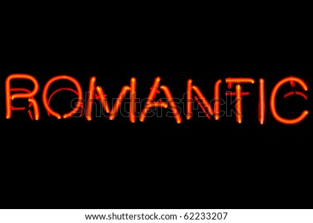 Red neon sign of the word 'Romantic' on a black background.