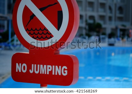 Red no jumping warning sign at the poolside - stock photo