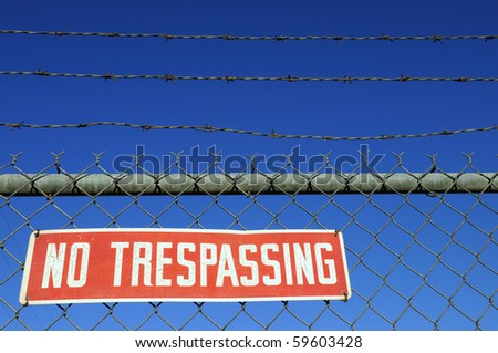 """Red """" NO TRESPASSING"""" warning sign on chain link fence - stock photo"""