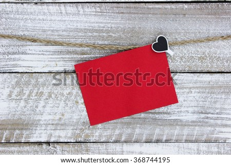 Red note card hanging on clothesline with heart and white rustic antique wood background; Valentine's Day and love concept - stock photo