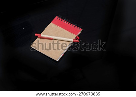 red notebook isolated on black background - stock photo