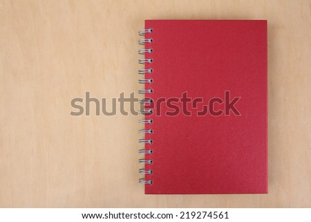 Red notebook paper on wood background - stock photo