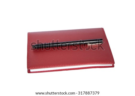 Red notebook with pen isolated on white background.