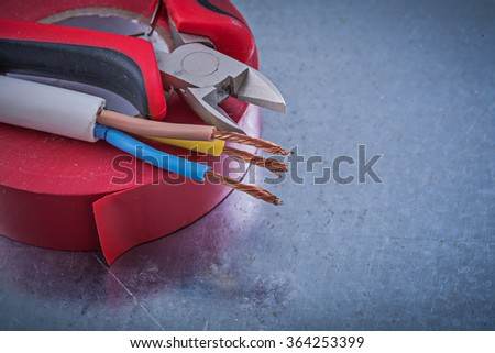 Red nsulation tape cutting pliers electric wires construction concept.