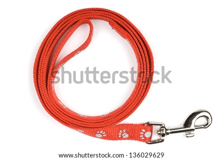 Red nylon dog lead or leash with paw print pattern on a white background. Soft shadow under lead. - stock photo