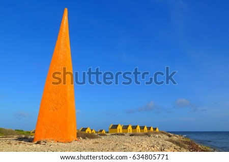 Red obelisk and small huts. Red salt work and slave huts. Stony beach with bright orange obelisk navigation point and small huts for workers and slaves. Old salt plantation picture.