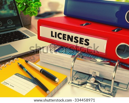 Red Office Folder with Inscription Licenses on Office Desktop with Office Supplies and Modern Laptop. Business Concept on Blurred Background. Toned Image. - stock photo