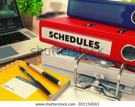 Red Office Folder with Inscription Schedules on Office Desktop with Office Supplies and Modern Laptop. Business Concept on Blurred Background. Toned Image. - stock photo