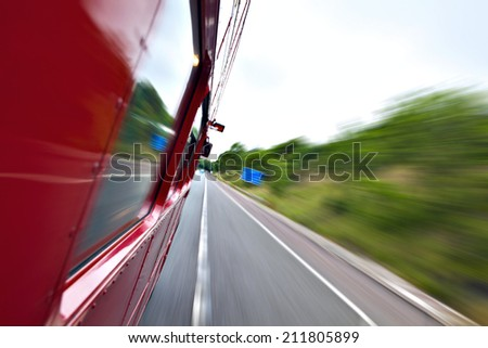 Red old bus going fast on the highway with motion blur background - stock photo