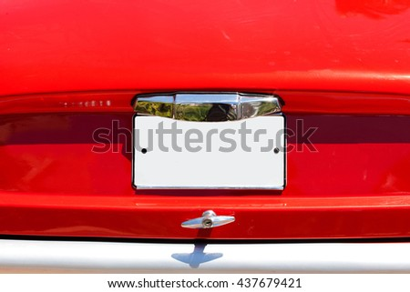 Red old car with empty license plate - stock photo