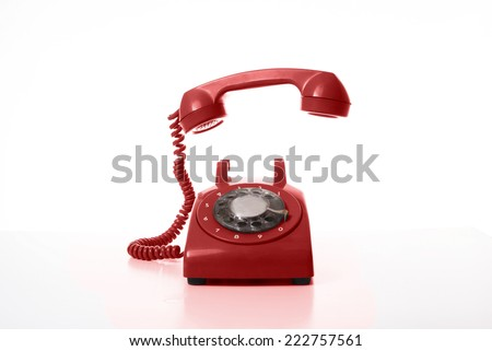 Red old dial-uptelephone, handset is on mid air.