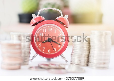 Red old fashioned alarm clock on time to work at make money. - stock photo