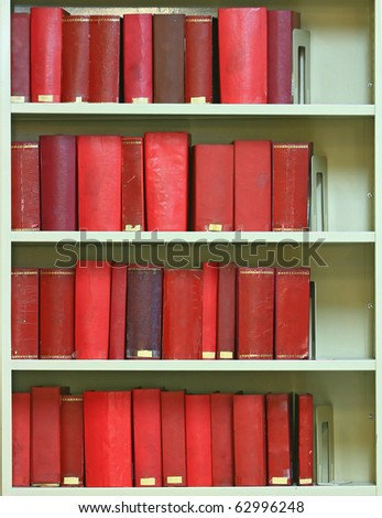 red old hardcover books on bookshelf in library - stock photo