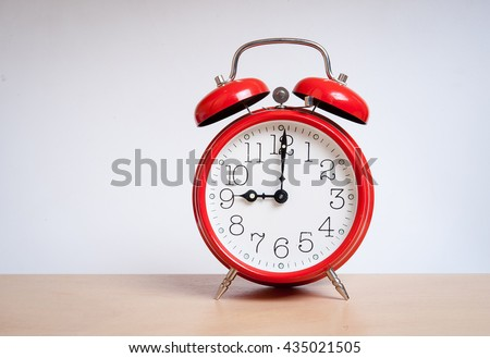 red old retro style alarm clock on  wood table. Alarm clock shows eight o`clock - stock photo