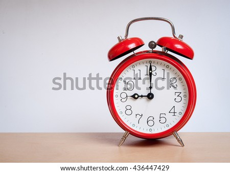 red old retro style alarm clock on wood table. Alarm clock shows seven o`clock