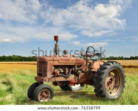 red old rusty tractor in a field - stock photo
