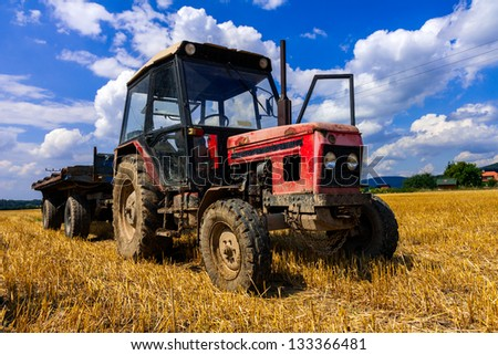 red old tractor in summer on field - stock photo