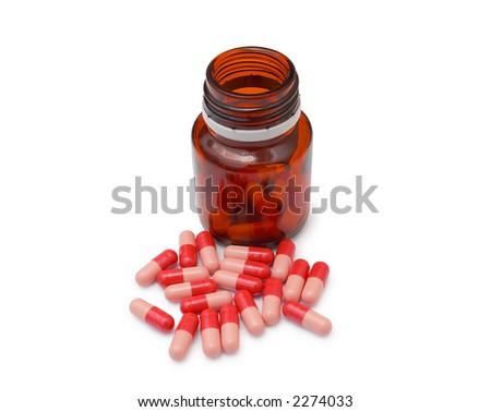 Red Omeprazol pills next to pill bottle - stock photo