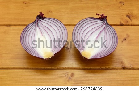 Red onion cut in half on a wooden table - stock photo