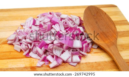 Red onion cuts and wooden spoon on a wooden board - stock photo