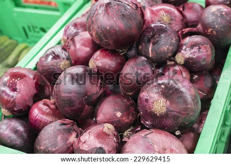 red onion in green crate