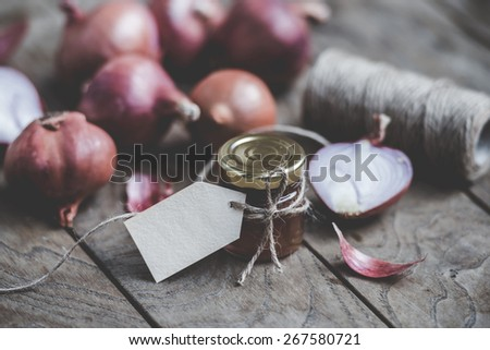 Red onion marmalade in a small glass jar on wooden table. Blank label provides copy space for a message. Toned image - stock photo