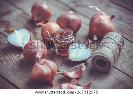 Red onion marmalade in a small glass jar on wooden table. Toned image - stock photo