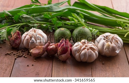red onion, red shallot, garlic, lime, green onion and celery on rustic wood background