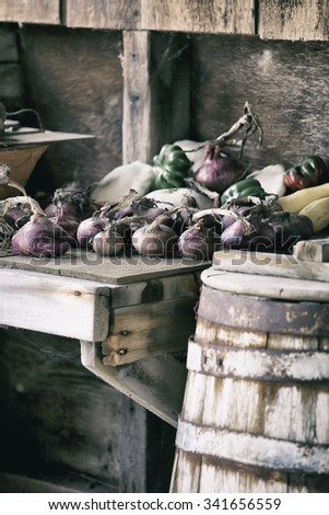 Red onions and other vegetables in a very rustic environment with old wood barrel and rough wood table. - stock photo