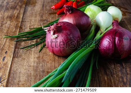 Red onions chili and bunch chives composition lying on the wooden table