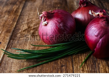 Red onions chilli garlic and bunch chives composition lying on the wooden table