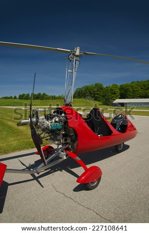 Red open-cockpit autogyro parked at the airfield